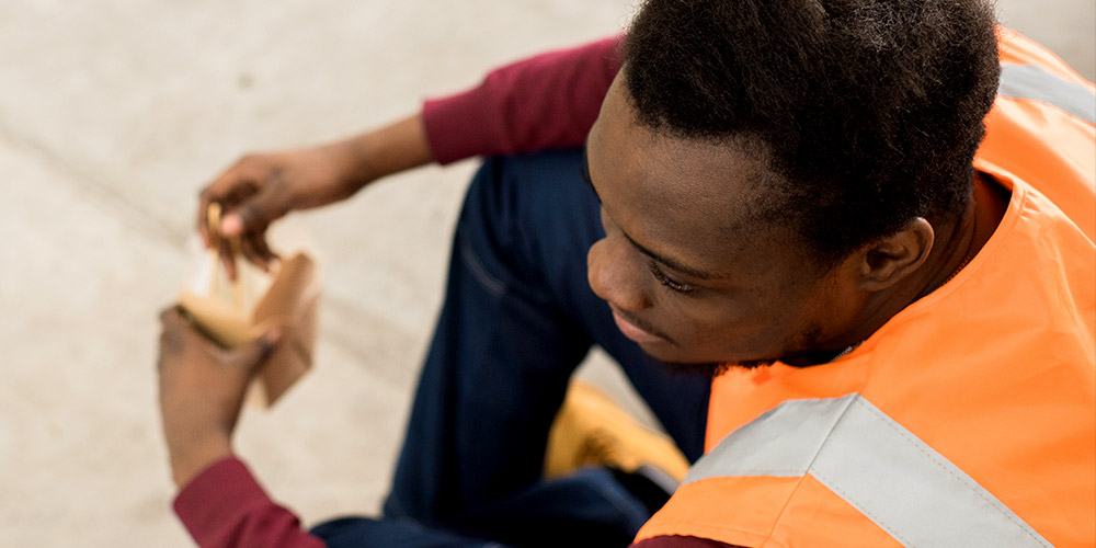 Innovative Learning Solutions Website Image African Truck Training Man Sitting Down Wearing Orange Vest