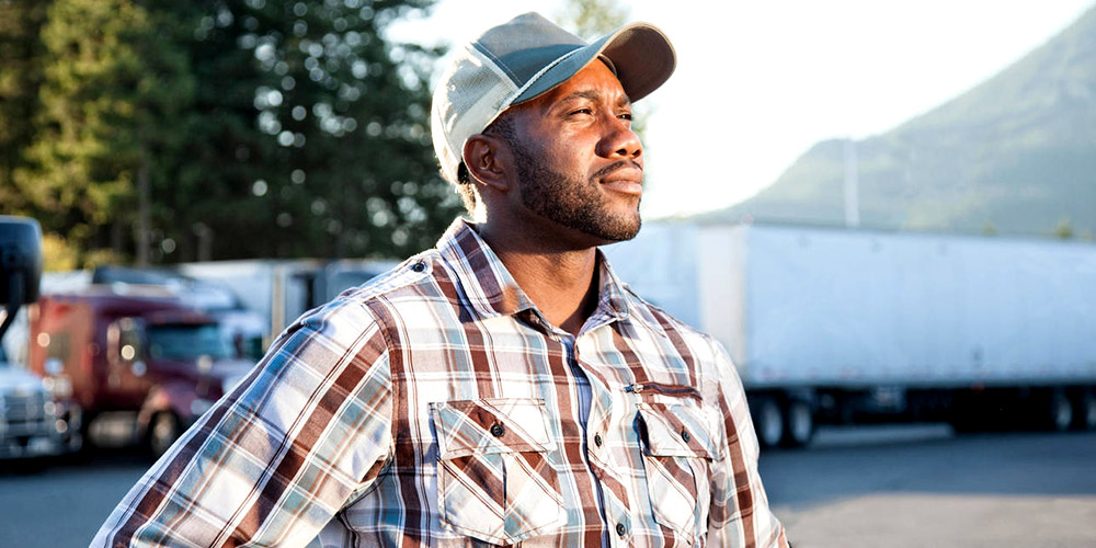 Innovative Learning Solutions_Website Images_Welcome Image African Truck Driver Wearing Cap Standing In Front Of Trucks